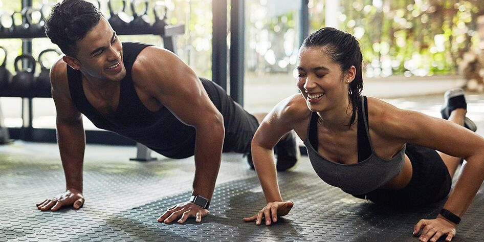 man and woman working out together, sweating and laughing at each other