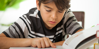 a concentrated boy reading a large book indoors
