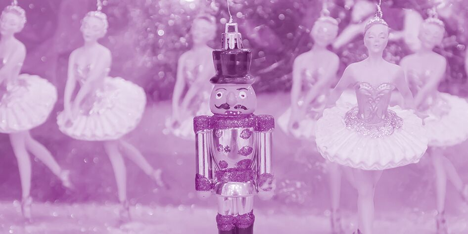 Nutcracker and ballet dancer ornaments hanging on a tree with a purple overlay